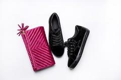 Czarni zamszowy sneakers i aksamitny purpury sprz?g?o nad bia?ym t?em zdjęcia stock