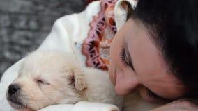 Czarnogłowa dziewczyna i biały szczeniak śpi wpólnie zbiory