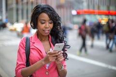 Czarny Afrykanin Amerykańskiej kobiety texting telefon komórkowy w mieście Obrazy Stock