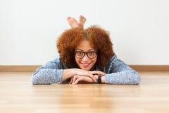 Czarny Afrykanin Amerykańskiej nastoletniej dziewczyny łgarski puszek na drewnianej podłoga Fotografia Royalty Free