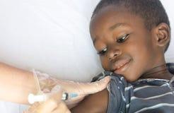 Czarny Afrykanin chłopiec dostaje medycznego zastrzyka jako opieka zdrowotna projekt dla Afryka Obrazy Royalty Free