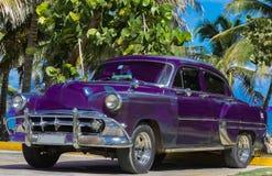 Czarny amerykański Oldtimer parkujący pod palmami blisko plaży w Varadero Kuba, Seria Kuba 2016 reportażu - Zdjęcia Stock