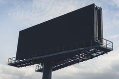 Czarny billboard przeciw jaskrawemu niebieskiemu niebu Zdjęcia Stock