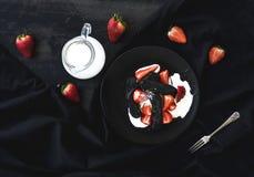 Czarny biscotti i truskawki deser z słodką śmietanką nad czarnym tłem Obrazy Royalty Free