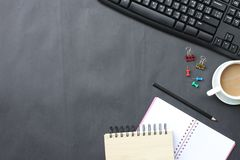 Czarny biurko z filiżanką, klawiaturą, notatnikiem i piórem umieszczającym wewnątrz, zdjęcia stock