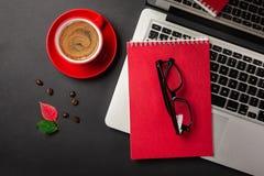 Czarny biurowego biurka st?? z pustego ekranu laptopem, notatnikiem, fili?anka kawy i innym biurem, obraz stock