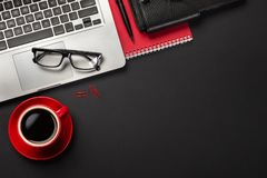Czarny biurowego biurka st?? z pustego ekranu laptopem, notatnikiem, mysz?, fili?anka kawy i innym biurem, Odg?rny widok obraz stock
