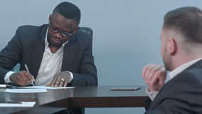 Czarny biznesmen podpisuje kontrakt i daje papierom partner Fotografia Stock