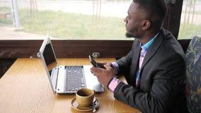 Czarny biznesmen pracuje na laptopie z smartphone w kawiarni i spojrzeniach przy okno zbiory wideo