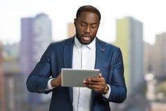 Czarny biznesmen z cyfrową pastylką Zdjęcie Stock
