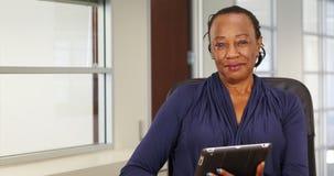 Czarny bizneswoman szczęśliwie używa jej pastylkę dla portreta podczas gdy pozujący Zdjęcie Stock