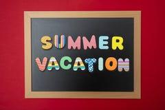 Czarny chalkboard z drewnianą ramą, teksta wakacje w kolorowych listach, czerwieni ścienny tło zdjęcie stock