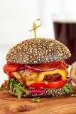 Czarny cheeseburger na drewnianej desce Obraz Stock