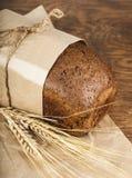Czarny chleb w papierowym kocowaniu z ucho banatka Fotografia Royalty Free