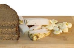 Czarny chleb z bekonem i czosnkiem na białym tle Zdjęcia Royalty Free