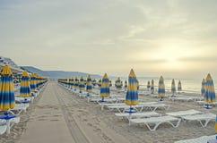 Czarny Denny brzeg przy wschodem słońca, plażowy piasek z parasolami Obraz Royalty Free