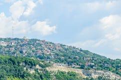 Czarny Denny brzeg, zieleni wzgórza z domami, błękit chmurnieje niebo Fotografia Stock