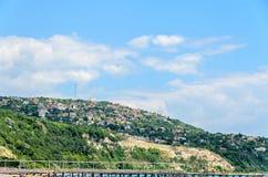 Czarny Denny brzeg, zieleni wzgórza z domami, błękit chmurnieje niebo Obrazy Stock