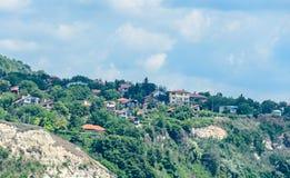 Czarny Denny brzeg, zieleni wzgórza z domami, błękit chmurnieje niebo Fotografia Royalty Free