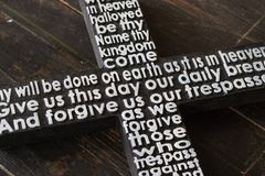Czarny drewniany krzyż z bielem władyki ` s modlitwa na podławym ciemnym drewnianym deski zakończeniu obrazy stock