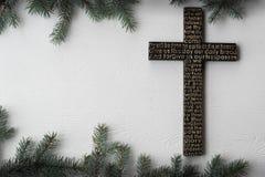 Czarny drewniany krzyż z władyki modlitwą na białej drewnianej desce z jedlinowym gałąź tłem fotografia stock