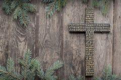 Czarny drewniany krzyż z władyki modlitwą na podławej ciemnej drewnianej desce z jedlinowym gałąź tłem obraz stock