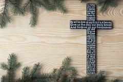 Czarny drewniany krzyż z władyki modlitwą na podławej drewnianej desce z jedlinowym gałąź tłem fotografia royalty free