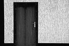 Czarny drzwi na szarości ścianie Zdjęcia Stock