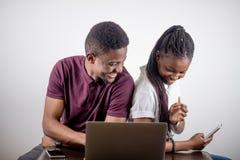 Czarny dziewczyny obsiadanie przed laptopem s patrzeje na ekranie Obrazy Stock