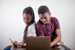 Czarny dziewczyny obsiadanie przed laptopem s patrzeje na ekranie Fotografia Stock