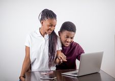 Czarny dziewczyny obsiadanie przed laptopem s patrzeje na ekranie Zdjęcia Stock