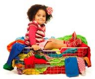 Czarny dziewczyny obsiadanie w koszu z odziewa Zdjęcie Stock
