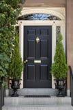 Czarny dzwi wejściowy z Białą Drzwiową ramą Greenery i Obraz Stock