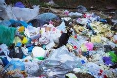 Czarny figlarki odprowadzenie przed stosem śmieci Obrazy Royalty Free
