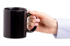 Czarny filiżanka kubek w żeńskiej ręce obraz stock