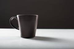 Czarny filiżanki ot biały stół Obraz Stock