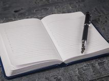 Czarny fontanny pióro z błękitnym Notepad na ciemnym drewnianym wieśniaka stole najlepszy widok Obraz Stock