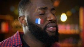 Czarny francuski futbolowy zwolennik z flagą na policzku nieszczęśliwym z drużynowym niepowodzeniem zbiory wideo