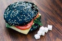 Czarny hamburger na desce drewno Zdjęcia Stock