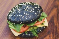 Czarny hamburger na desce drewno Zdjęcie Royalty Free