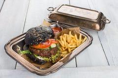 Czarny hamburger na rzemiosło papierze, biały drewno stół Zdjęcia Stock