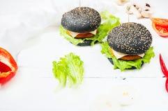 Czarny hamburger z cutlet, serem, pomidorem i sałatką kurczaka, słuzyć na białym drewnianym tle obraz stock