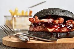 Czarny hamburger z francuzów dłoniakami na tle zdjęcia stock