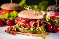 Czarny hamburger z mięsnym pasztecikiem, ser, pomidory, majonez Ciemny drewniany wieśniaka stół Nowożytny fasta food lunch zdjęcie stock