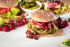 Czarny hamburger z mięsnym pasztecikiem, ser, pomidory, majonez Ciemny drewniany wieśniaka stół Nowożytny fasta food lunch fotografia stock