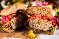 Czarny hamburger z mięsnym pasztecikiem, ser, pomidory, majonez Ciemny drewniany wieśniaka stół Nowożytny fasta food lunch obrazy stock