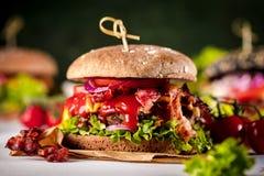 Czarny hamburger z mięsnym pasztecikiem, ser, pomidory, majonez Ciemny drewniany wieśniaka stół Nowożytny fasta food lunch obrazy royalty free