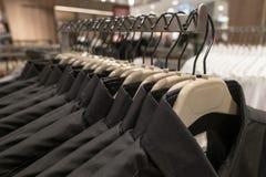 Czarny i błękitny koszulowy zrozumienie na stojaku, mężczyzna ` s koszula na wieszakach w garderobie Obrazy Stock