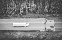 Czarny i biały abstrakcjonistyczny wizerunek biel ciężarówka logisctic firma z ładunkiem i swój dużą sylwetką jedzie na th zdjęcia royalty free