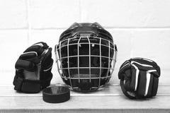 Czarny i biały fotografia dzieciaka ` s hokejowy wyposażenie: łuny, hełm i krążek hokojowy, Przekładnia jest na ławce Obrazy Stock
